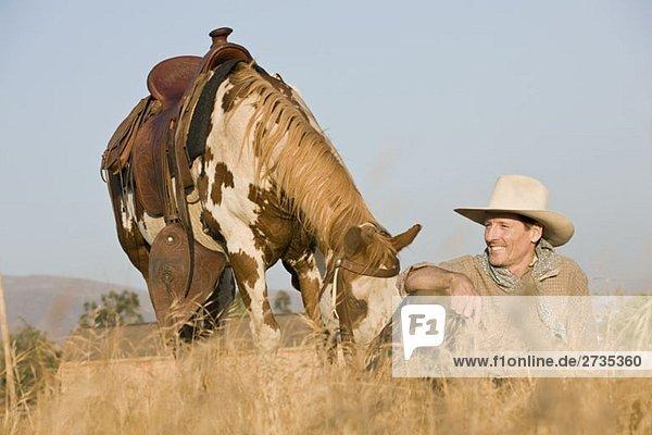 Ein Cowboy sitzt mit seinem Pferd im langen Gras. Ein Cowboy sitzt mit seinem Pferd im langen Gras.