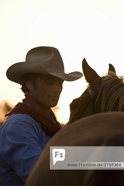 Ein Cowboy steht neben seinem Pferd. Ein Cowboy steht neben seinem Pferd.
