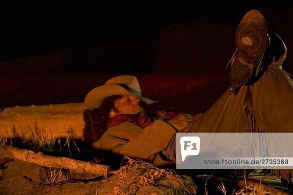 Ein Cowboy  beleuchtet von einem Lagerfeuer  während er schläft. Ein Cowboy, beleuchtet von einem Lagerfeuer, während er schläft.