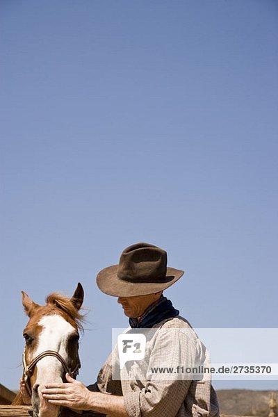 Ein Cowboy streichelt ein Pferd Ein Cowboy streichelt ein Pferd