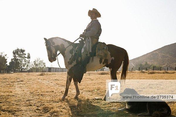 Profil eines Cowboys auf einem Pferd sitzend Profil eines Cowboys auf einem Pferd sitzend