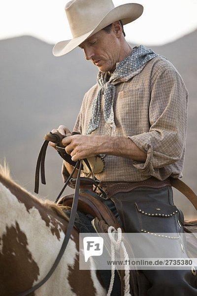 Ein Cowboy sitzt auf seinem Pferd. Ein Cowboy sitzt auf seinem Pferd.
