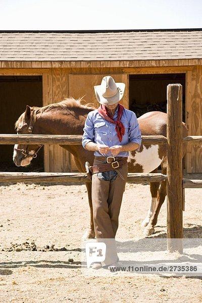 Ein Cowboy  der sich auf einer Ranch an einen Zaun lehnt. Ein Cowboy, der sich auf einer Ranch an einen Zaun lehnt.