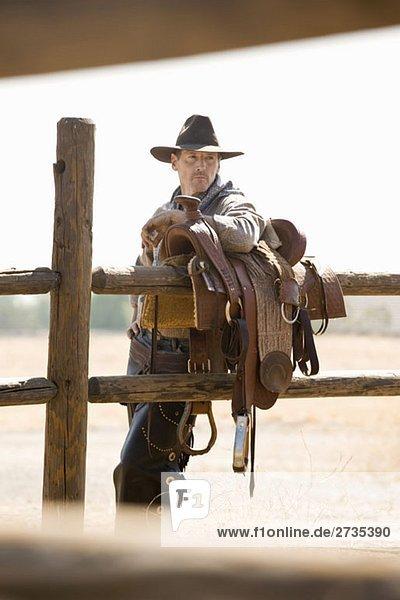 Ein Rancher  der sich gegen einen Sattel auf einem Zaun lehnt. Ein Rancher, der sich gegen einen Sattel auf einem Zaun lehnt.