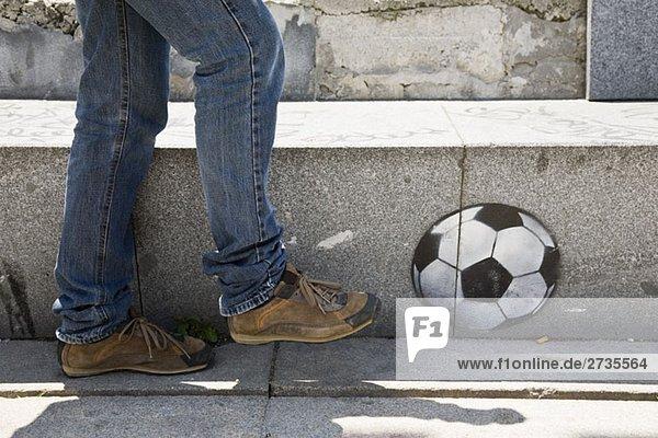 Eine Person  die gestikuliert  um einen an die Wand gemalten Fußball zu treten.