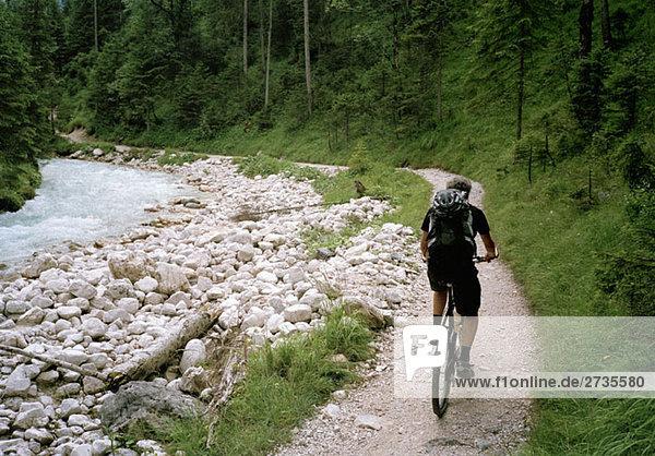 A man cycling alongside a river  Austria