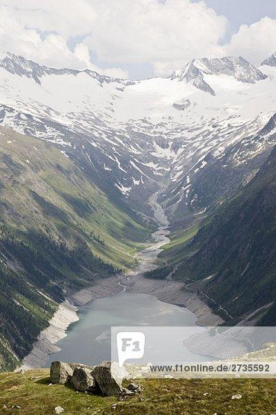 Blick auf ein Tal und Stausee in den österreichischen Alpen