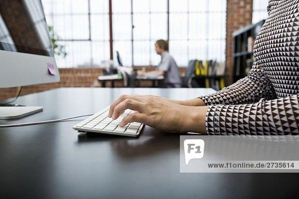 Eine Frau  die einen Computer in einem Büro benutzt.