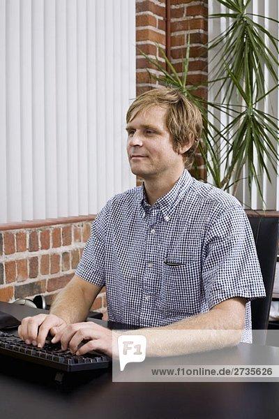 Ein Mann  der auf einer Computertastatur schreibt.