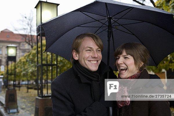 Junges Paar lacht unter einem Regenschirm