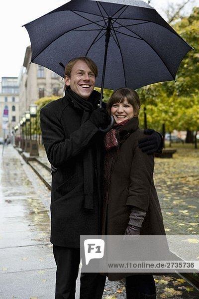 Junges Paar steht und hält Regenschirme