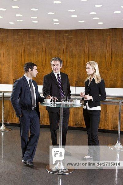 Drei Geschäftsleute stehen in einem Café.