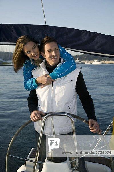Ein Paar  das sich am Steuer einer Yacht umarmt.