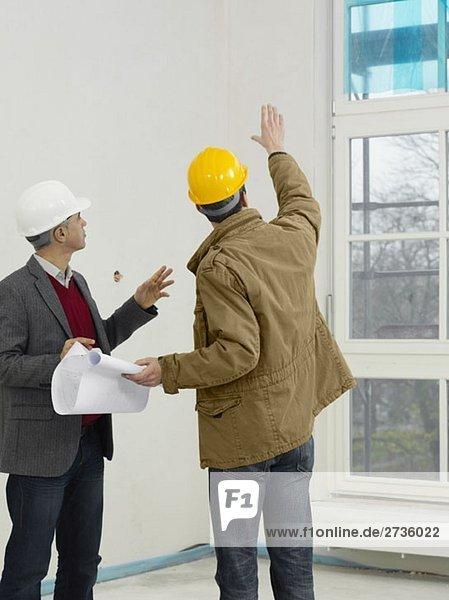 Ein Architekt im Gespräch mit einem Bauarbeiter