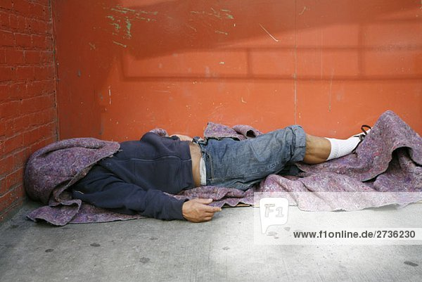 A homeless person sleeping on the floor