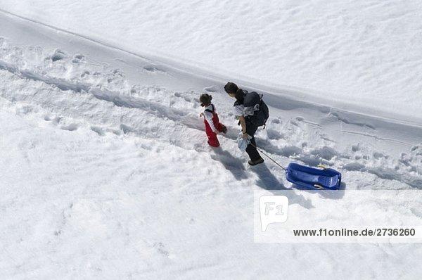 Eine Frau und ein Mädchen  die mit einem Schlitten im Schnee laufen.