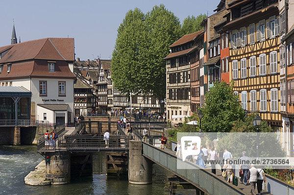 People walking on bridge in front of timber framed houses  Strasbourg  Germany