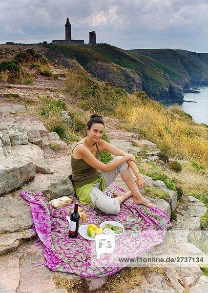 Junge Frau mit einem Picknick in einer Felswand Cape Fréhel  Cancale  Ile-et-Vilaine  Bretagne  Frankreich  Europa