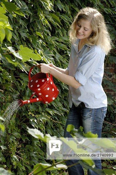 Frau mit Gießkanne wässert Garten