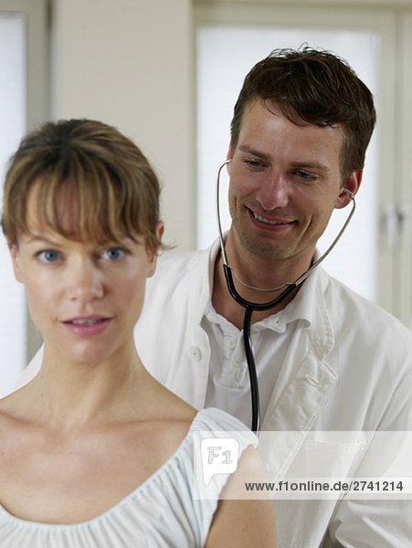 Arzt hört Patientin mit Stethoskop ab