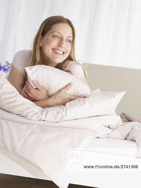 Junge Frau behaglich im Bett