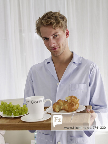 Junger Mann trägt Frühstückstablett