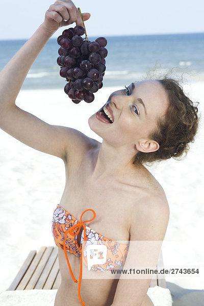 Frau isst Trauben