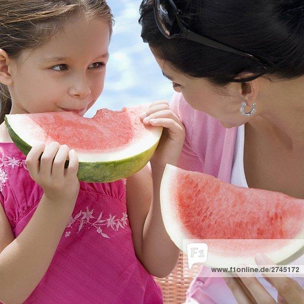 Nahaufnahme einer jungen Frau mit ihrer Tochter Essen Wassermelone Scheiben