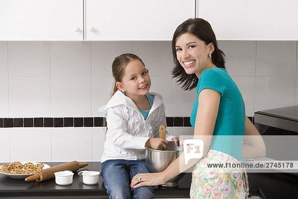 Junge Frau machen Cookies mit ihrer Tochter in der Küche