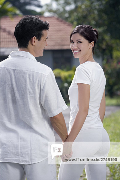 junges Paar stehen in einem Garten und lächelnd