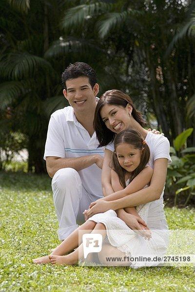 Porträt eines jungen Paares mit ihrer Tochter in einem Garten sitzen