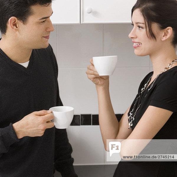 junges Paar hält Tassen Tee und Blick auf einander