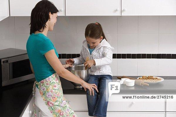 Seitenansicht einer jungen Frau mit ihrer Tochter in der Küche Essen zubereiten
