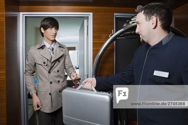 Zimmerservice Mann Übergabe einer Aktentasche an einem Geschäftsmann