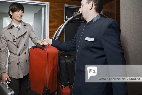 Zimmerservice Mann Übergabe Gepäck an einem Geschäftsmann