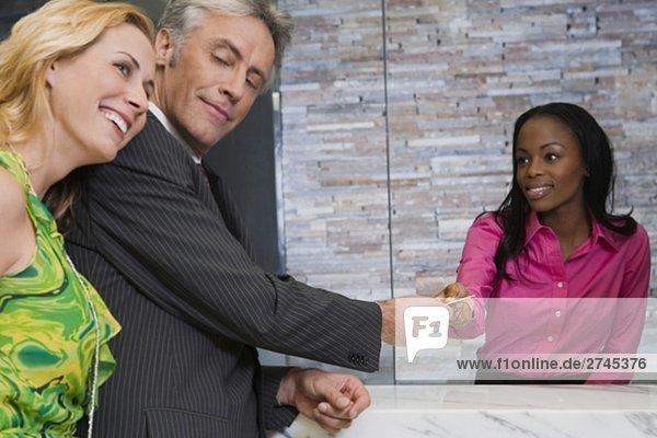 Älterer Mann geben eine Kreditkarte  ein Hotel-Rezeption