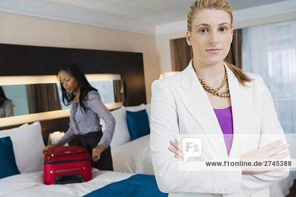 Portrait des ständigen mit ihren Armen geschäftsfrau überquerte mit einem anderen geschäftsfrau Verpackung ihr Gepäck