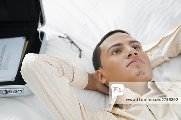 Kaufmann liegend auf dem Bett und denken