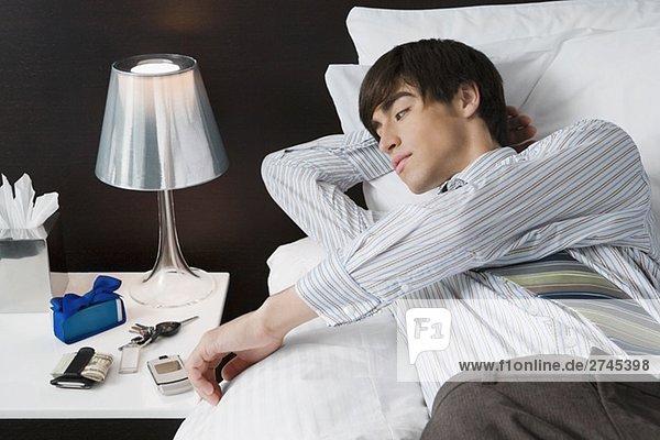 Kaufmann liegend auf dem Bett und Blick auf einem Mobiltelefon