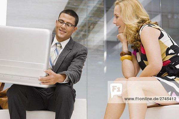 Unternehmer hält eine Aktentasche mit einer Reifen Frau neben ihm sitzt