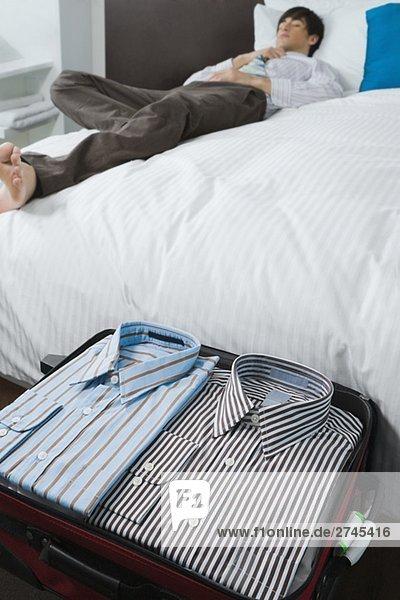 Hemden in einem Koffer und ein Geschäftsmann auf dem Bett schlafen