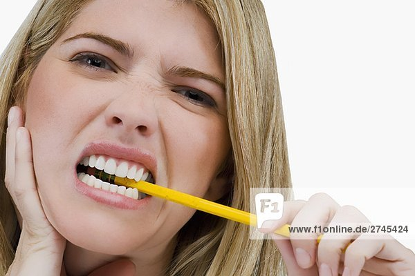 Portrait of a young woman biting a pencil