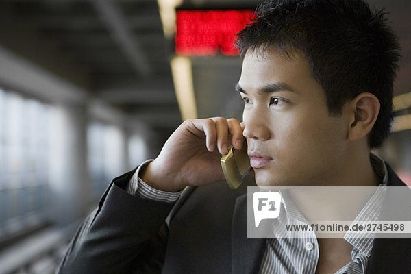 Close-up of a businessman talking on a mobile phone at a subway station