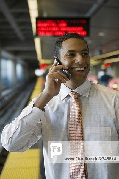 Nahaufnahme eines Kaufmanns sprechen auf einem Mobiltelefon in einer u-Bahn-Station
