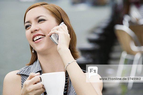 Nahaufnahme of a junge Frau hält eine Kaffeetasse und sprechen auf einem Mobiltelefon