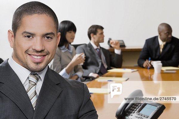 Porträt von einem Kaufmann lächelnd mit seinen Kollegen diskutieren im Hintergrund