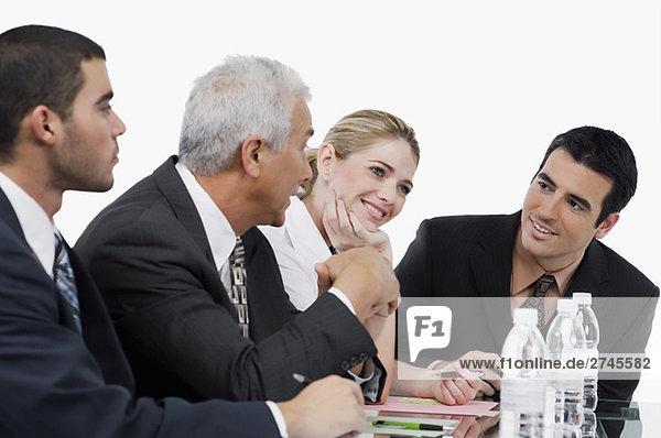 Drei Geschäftsmänner und eine geschäftsfrau bei einem Treffen in einem Konferenzraum