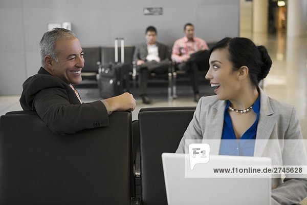 Side profile of a businessman with a businesswoman looking at each other and smiling at an airport