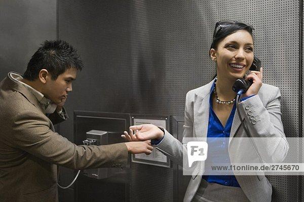 Geschäftsfrau und sprechen auf Münztelefonen auf einem Flughafen Geschäftsmann