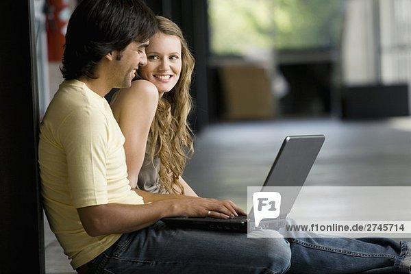 Junge Frau sitzend mit einem jungen Mann arbeiten auf einem laptop